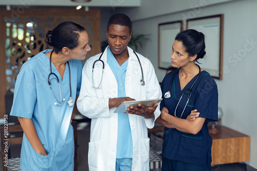 Doctors discussing over digital tablet in the hospital