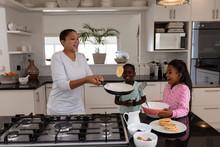 Mother And Children Preparing Food On A Worktop In Kitchen