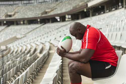 Upset African American male rugby player sitting with rugby ball in stadium