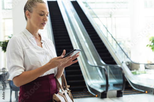 Young businesswoman looking at mobile phone while standing in modern office