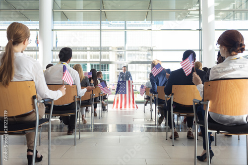 Group of diverse business people with flags listening mature businessman presentation