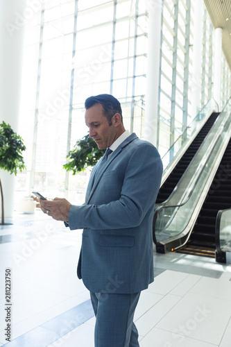 Mature businessman looking at mobile phone while standing in modern office