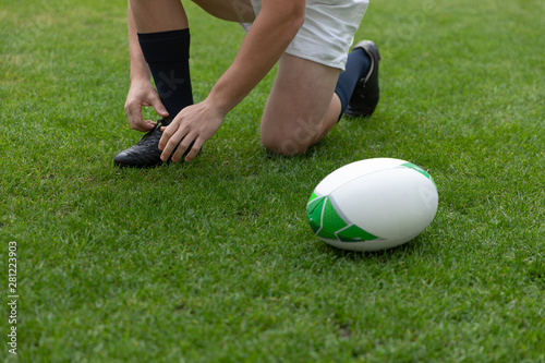 Caucasian male rugby player tying shoelaces in the stadium