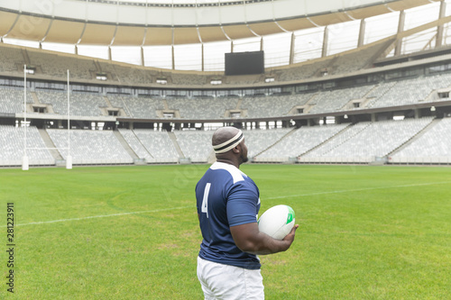 African American rugby player standing with rugby ball in the stadium