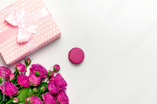 Foto auf Gartenposter Macarons Gift box with ribbon, bright pink roses, cake macaron or macaroon on light gray background. Flat lay, top view, copy space. Greeting card for Birthday, Womens or Mothers Day. Flowers composition