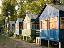 Row Of Old Vintage Wooden Colorful Small Houses In The Woods With Weathered Peeled Painting