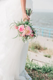 Fototapeta Kawa jest smaczna - Bride with a wedding bouquet in his hands with pink flowers and succulents