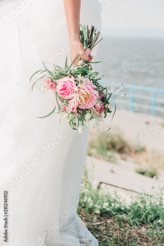 Bride with a wedding bouquet in his hands with pink flowers and succulents