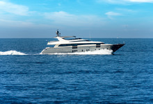 White, Gray And Black Luxury Yacht In Motion On The Mediterranean Sea, Side View, With Blue Sky And Clouds Over The Horizon. Liguria, Italy, Europe