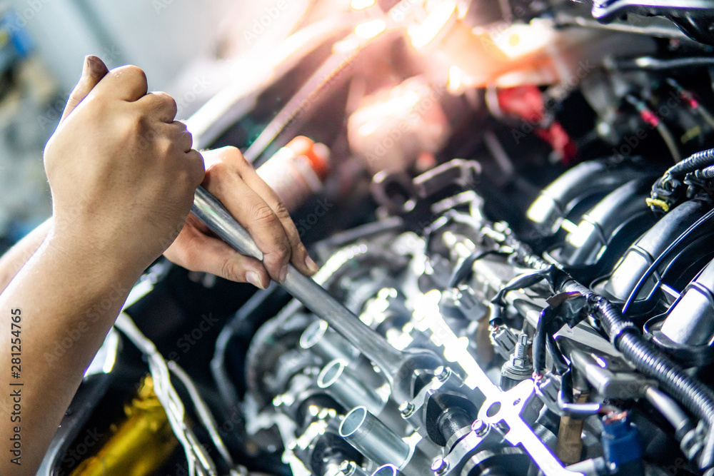 Fototapety, obrazy: Male hand of auto mechanic fixing car engine with wrench in the garage. Automobile industry concept