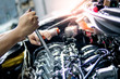 Male hand of auto mechanic fixing car engine with wrench in the garage. Automobile industry concept