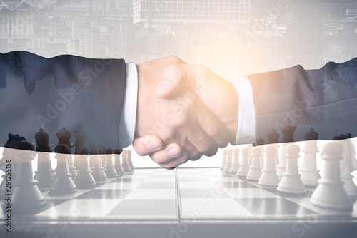 Fotomural  The double exposure image of the businessman handshaking with another one during sunrise overlay with cityscape and chess board image