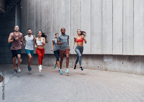 Cadres-photo bureau Jogging Full length of young people in sports clothing jogging while exercising outdoors