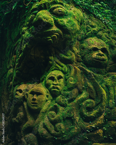 Fotografering Carving demons faces on wall background covered with moss texture in Bali