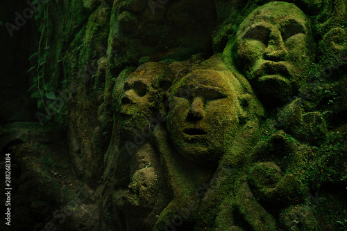 Fotografía Carving demons faces on wall background covered with moss texture in Bali