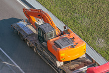 Truck With A Long Trailer Platform For Transporting Heavy Machinery, Loaded Excavator. Highway Transportation.