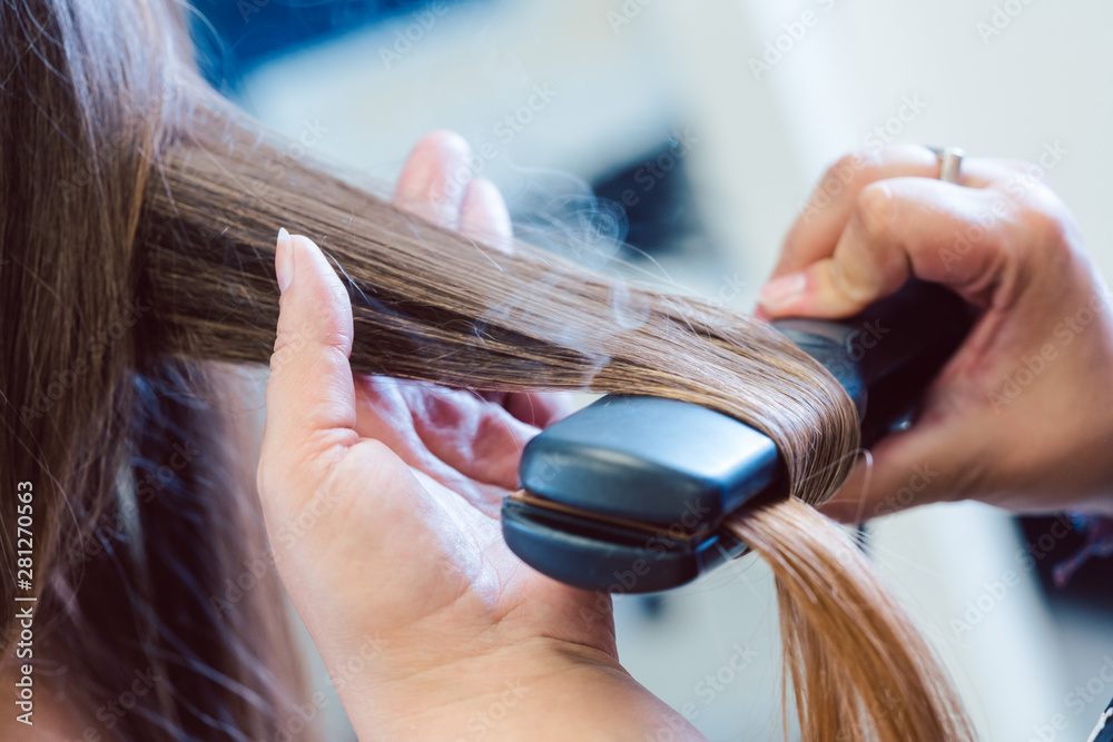 Fototapeta Hairdresser using flat iron on hair of woman customer