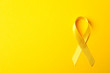 Yellow awareness ribbon on color background, space for text