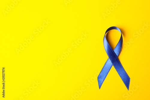 Fototapeta Blue awareness ribbon on yellow background, space for text