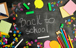 school supplies: multicolored wooden pencils, notebook, paper stickers, paper clips, pencil sharpener and white chalk inscription