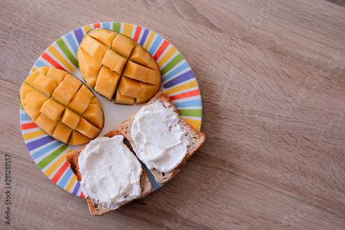 Obraz na plátně Cheese spread toasts with mango cut in cubes on a colorful plate on a wooden tab