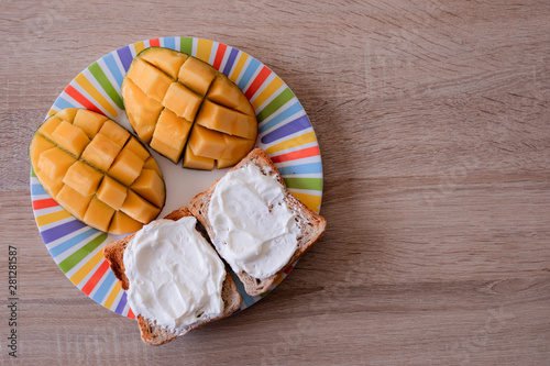 Fotografie, Obraz Cheese spread toasts with mango cut in cubes on a colorful plate on a wooden tab