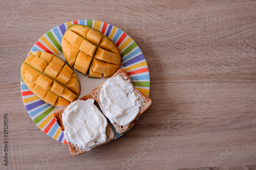 Fototapeta Cheese spread toasts with mango cut in cubes on a colorful plate on a wooden tab