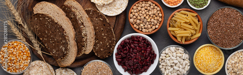 Stampa su Tela  Various grains, beans, nut and bread on wooden background