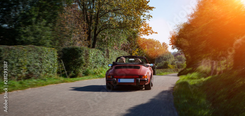 sports car drinving on a road on summer day Wallpaper Mural