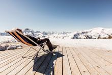 Austria, Damuels, Senior Man Relaxing In Deckchair On Sun Deck In Winter Landscape