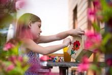 Girl Painting Red Flower On A Birdhouse