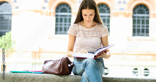 Poster de jardin Pain Beautiful female college student reading a book on a bench in a park