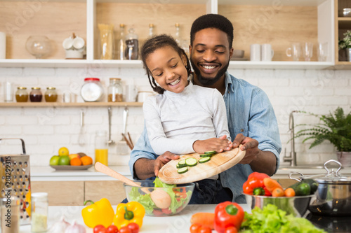 Daddy and daughter making fresh salad in kitchen Wallpaper Mural