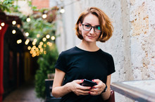 Young Hipster Girl In Glasses With Short Haircuts Use Smartphone And Sitting In Outdoor Street Cafe