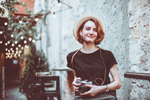 Carta da parati  Young hipster female journalist with retro camera  sits on a chair and smiles ou