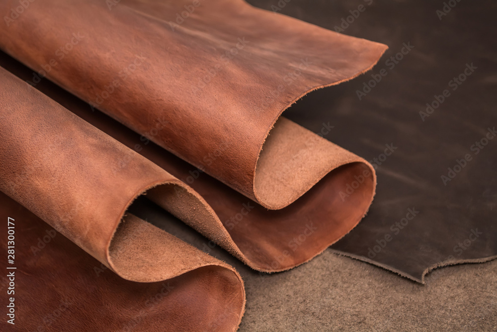 Fototapeta Rolls of natural brown and black leather. Materials for leather craft