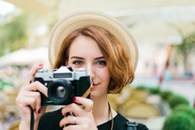 Closeup Portrait Of A Young Hipster Woman In Hat With Retro Camera Outdoors