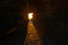 The Rays Of The Setting Sun Shine Through The Narrow Long Arch Of The Building Of The Monastery On Mount Athos