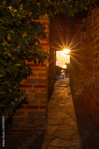 Photo The rays of the setting sun shine through the narrow long arch of the building o