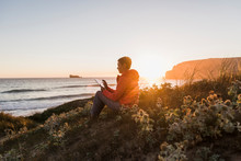 France, Bretagne, Crozon Peninsula, Woman Sitting At The Coast At Sunset Using Tablet