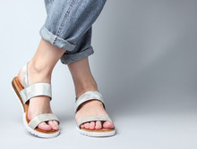 Fragment Of Female Legs In Blue Jeans And Trendy Leather Sandals On White Background. Women's Stylish Summer Shoes. Minimalistic Fashion Shot