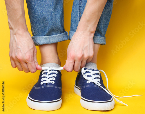 Fotografia  Woman tying shoelace of fashionable hipster sneakers over yellow background