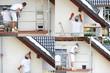 Malowanie wałkiem elewacji budynku na rusztowaniu.