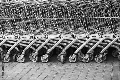 Shopping carts arranged in a row on the street near the supermarket.Close up wheel of shopping cart. Concept of shopping.