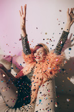 Smiling Young Person In Bright Fur Coat Between Tossing Confetti