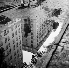 Reflection In A Puddle Of A Man Walking On A Wet City Street