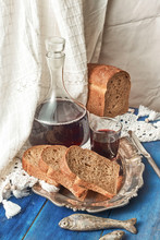 A Carafe And A Glass Of Red Wine Are Slices Of Rye Rural Bread O