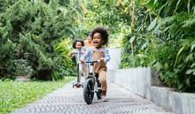 Children Enjoying Riding A Bike And A Scooter