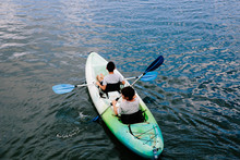 Two Young Boys Kayaking In Ultra Blue Waters