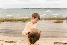 Boy Holding A Horseshoe Crab On The Beach